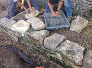 Building a Lannon Stone Retaining Wall- Mortaring the Top Row for Strength